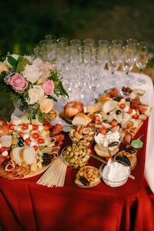 Стол с красной накидкой и пустыми бокалами из-под шампанского, подается с мясным сыром и фруктовыми нарезками