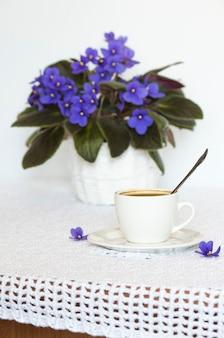 아프리카 보라색 꽃과 블랙 커피 한 잔이 있는 흰색 식탁보가 있는 테이블.