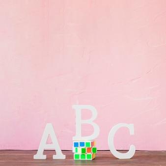 ピンクの壁の近くのアルファベットとルービックキューブのテーブル