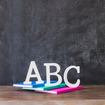 Table with alphabet letters on books near blackboard