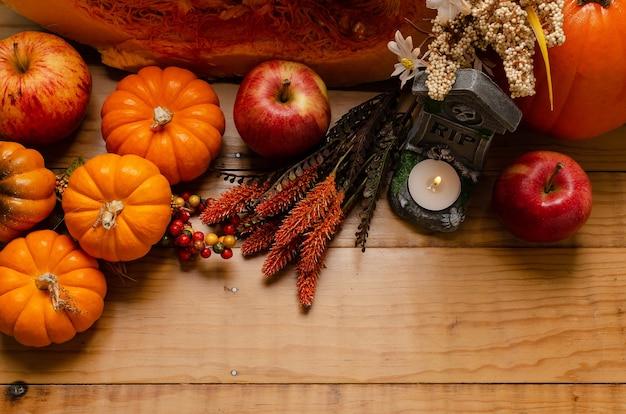 Стол с украшениями на осень и хэллоуин с цветами тыквы и свечой