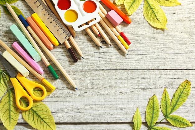 Стол с осенними листьями и разными школьными принадлежностями. свободное место для текста.