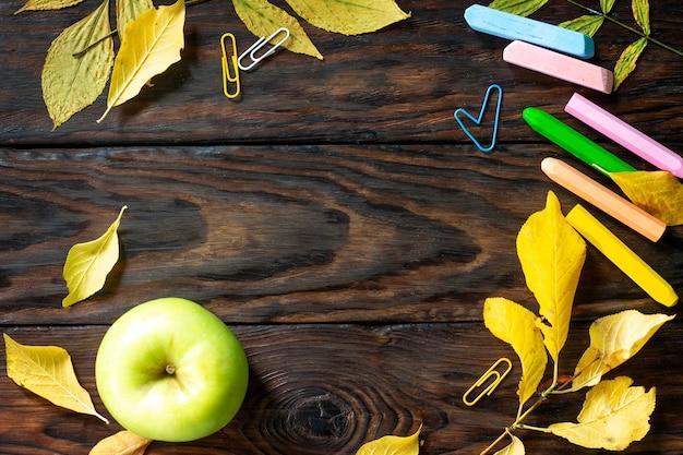 Стол с осенними листьями, яблоком и школьными принадлежностями плоский вид сверху с копией пространства