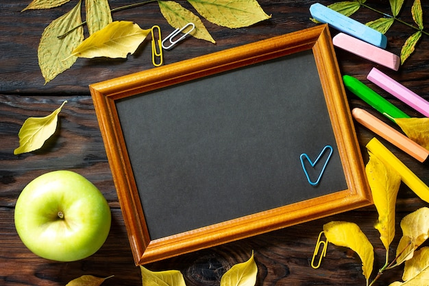 Table with autumn leaves note pad apple  and school supplies free space for your text