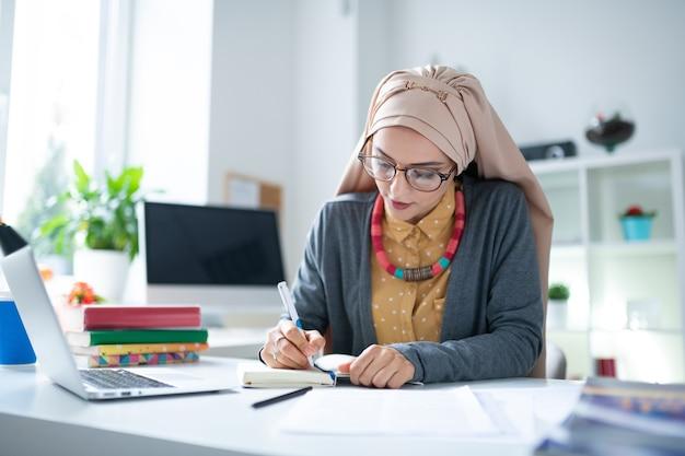 本のあるテーブル。本を持ってテーブルに座って仕事をしているヒジャーブを身に着けている忙しいイスラム教徒の教師