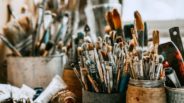 Table with brushes and tools in an art workshop. background.
