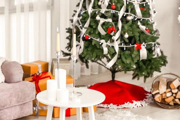 집에 촛불과 크리스마스 트리가 있는 테이블. 축제의 방 인테리어