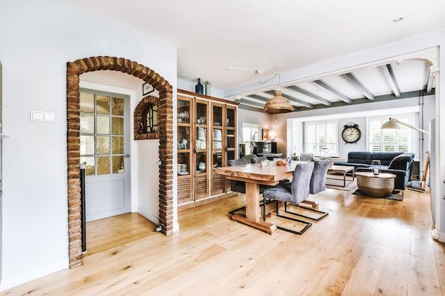 食器棚の近くにある椅子と自宅のダイニングルームのレンガで飾られたアーチ型の出入り口のテーブル