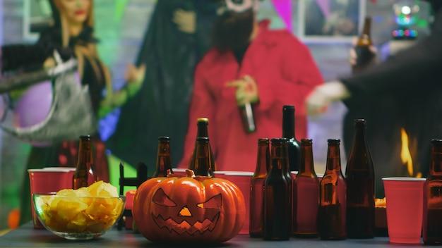 ダンスパーティーでハロウィーンを祝う人々のグループのためのチップスとビールのテーブル
