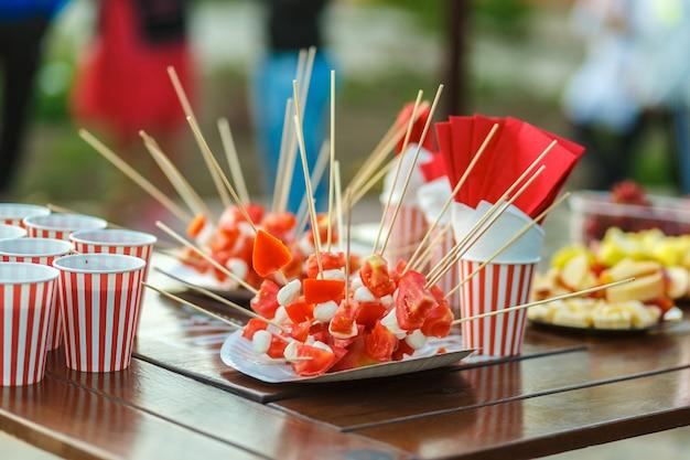 色付きの甘いおやつが入ったテーブル。野外パーティー。