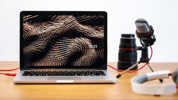 コンテンツクリエーターのものを含むテーブル。ノートパソコン、マイク、カメラレンズ、ヘッドフォン。家で働く