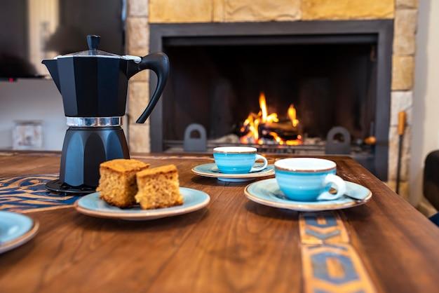 Стол с чашками, кофейник и камин