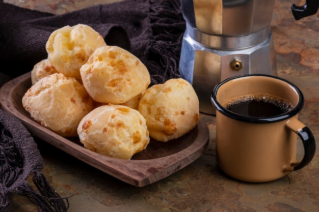 Стол с восхитительным сырным хлебом, кофейной кружкой и традиционной кофеваркой.