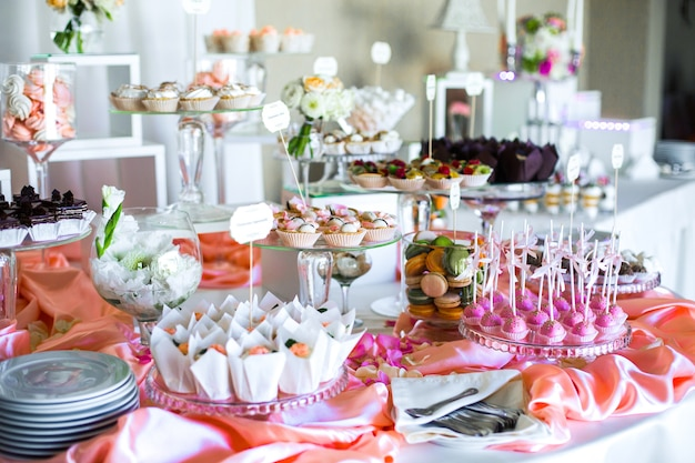 Table with delicious sweets covered with pink silk