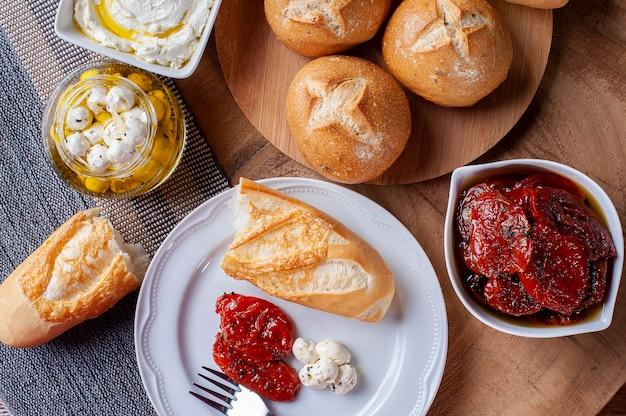 Стол с разными закусками. хлебное ассорти, вяленые помидоры, два вида творога.