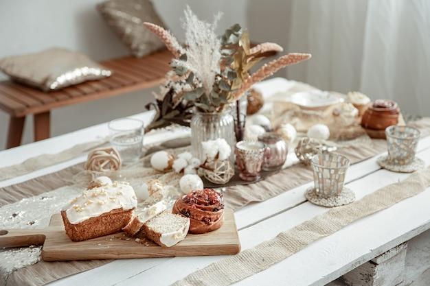 イースターの装飾要素とお祝いのペストリーのテーブル。居心地の良い家の構成。