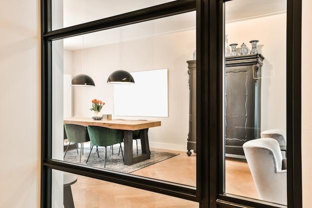 Стол с цветами и стульями и элегантный шкаф рядом с творческой росписью и светящимися лампами за окном в столовой дома