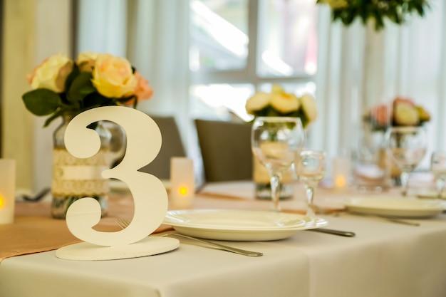 食物と結婚式の花を持つテーブル。結婚式を祝うための花とレストランのアクセサリーホールで上品に装飾されたスタイリッシュ。