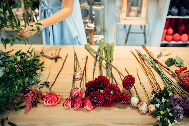 花屋でさまざまな種類の新鮮な花を持つテーブル