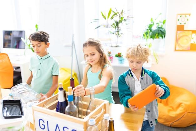 ガラスのテーブル。廃棄物の分別を勉強しているガラス瓶とテーブルの近くに立っているスマートなハンサムな学童