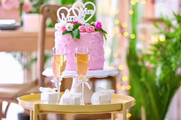 Table with glasses of champagne and delicious cake on lesbian wedding