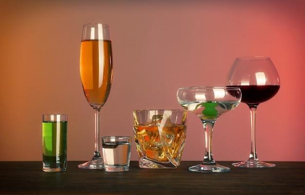 Стол с бокалами вина и спиртных напитков на цветном фоне