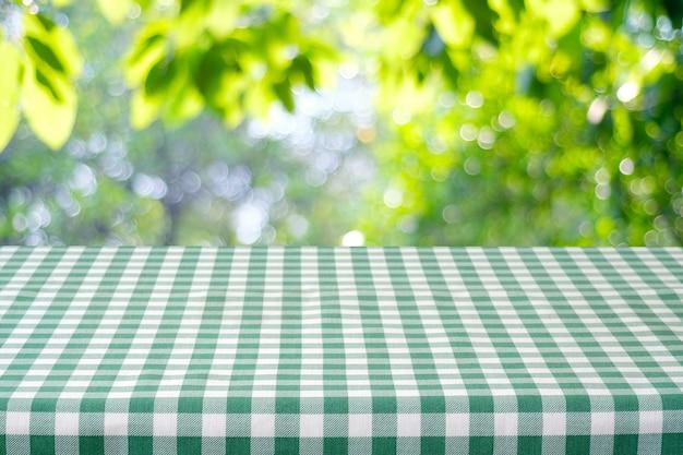 음식과 제품 디스플레이 몽타주에 대 한 bokeh 배경 위에 녹색 식탁보와 테이블.