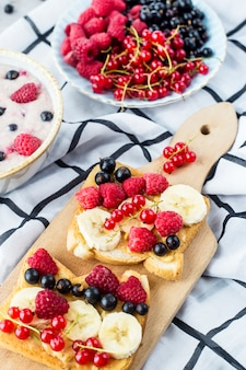 A table with a healthy summer breakfast - oatmeal with berries, currants and raspberries