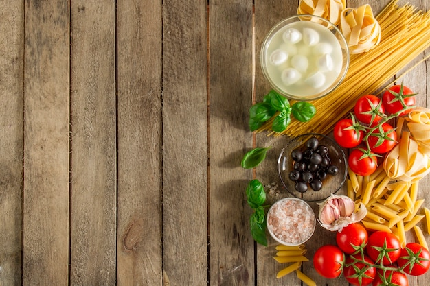 Table with ingredients to prepare italian pasta