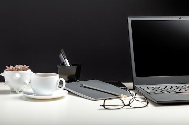 원격 작업 또는 연구를 위한 노트북, 커피 잔이 있는 테이블. 블랙 노트북 빈 디스플레이 템플릿