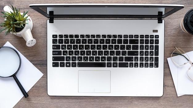 라이프 스타일 것들과 테이블. 노트북, 안경, 돋보기 나무 테이블에 장식. 평면도