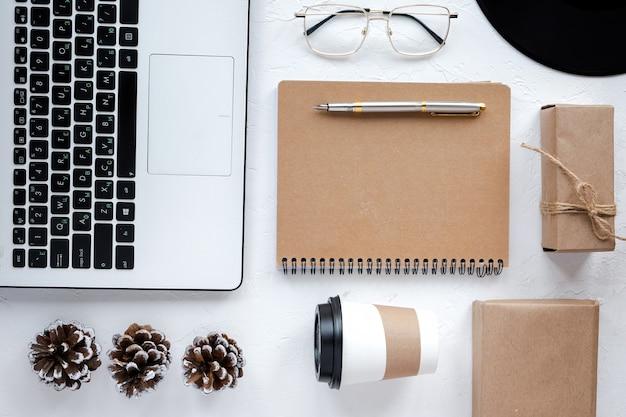 ライフスタイルのものとテーブル。ノートパソコン、ペン付きメモ帳、一杯のコーヒー、グラス、装飾品。上面図