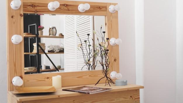 흰색 벽 근처에 메이크업 제품과 거울이 있는 테이블. 드레스룸 인테리어입니다. 여자 침실의 현대적인 인테리어