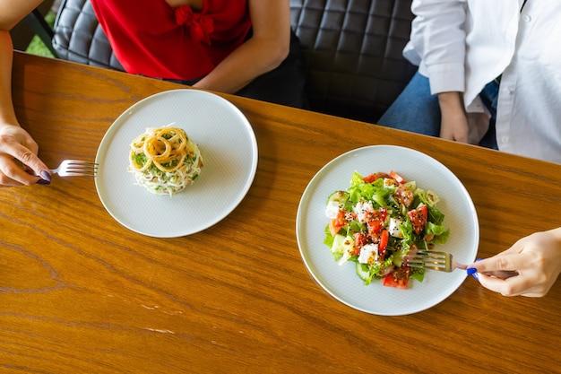 Стол с видом сверху много салатов. различные салаты на бетонном столе, вид сверху. овощной салат, салат с копченым лососем, севиче и страчателлой.