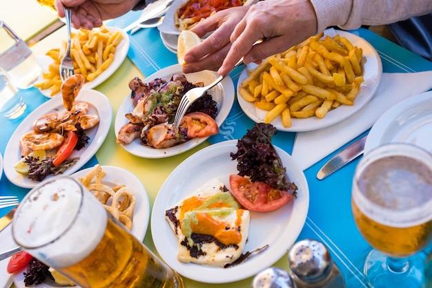 魚のような海産物のテーブル-クローズアップとテーブルの真ん中から食べ物を取っている手の肖像画-ビーチのレストラン