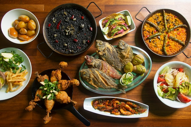 Table with meals from the sea and land, fried fish and paella.