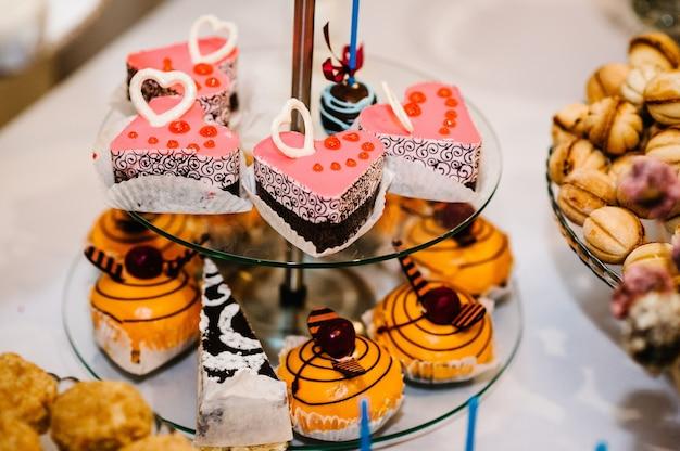 머핀, 케이크, 과자, 사탕, 뷔페가있는 테이블. 결혼식 연회장을위한 파티 케이크를위한 디저트 테이블. 확대. 캔디 바. 맛있게 꾸며졌습니다.