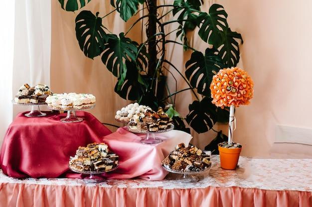 マフィン、ケーキ、お菓子、キャンディー、ビュッフェのテーブル。結婚式の宴会エリアのパーティーグッズのデザートテーブル