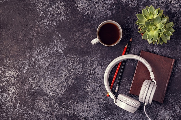 Table with notepad, headphones and coffee