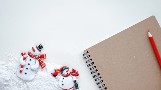 Table with notepad, a pencil, snowmen and snow on a table. top view