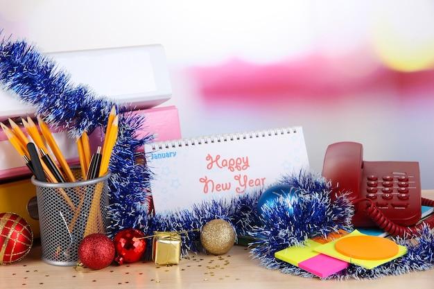 Стол с канцелярскими принадлежностями, календарем и рождественской мишурой крупным планом