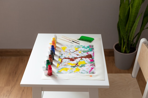 墨流し技法で描画するためのペイントとツールを備えたテーブル
