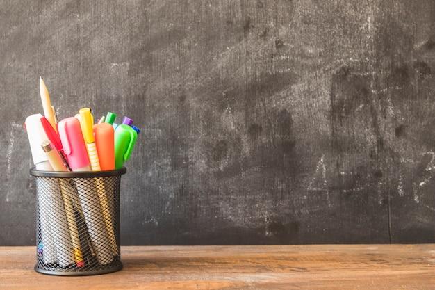Table with pencil cup near blackboard