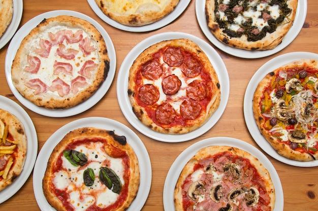 Стол с пиццей разных вкусов, вид сверху.