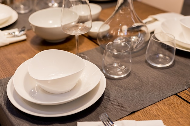 Table with plates and glasses before a party.piles of white ceramic tableware, plates, saucers, cups on a wooden table. kitchenware.festive table