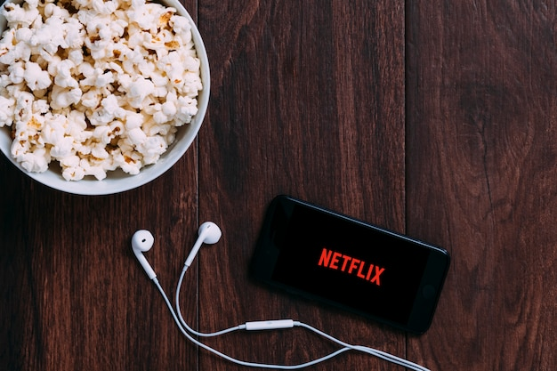 Table with popcorn bottle and netflix logo on apple iphone and earphone.