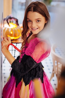 Table with pumpkin. beaming happy dark-haired girl wearing pink and black halloween dress standing near table with pumpkin