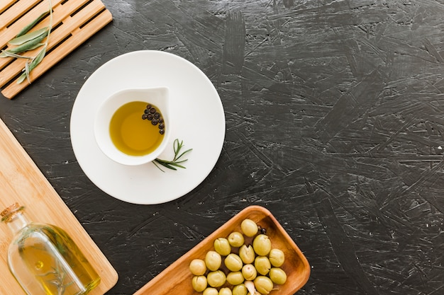 Table with sauceboat with oil and olives