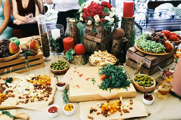 Table with snacks, fruits and cheese on large beige table