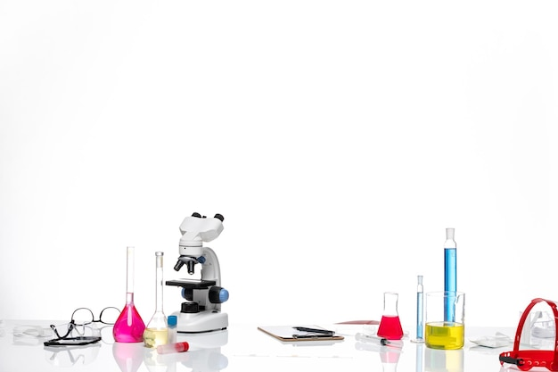 Table with solutions and microscope on white